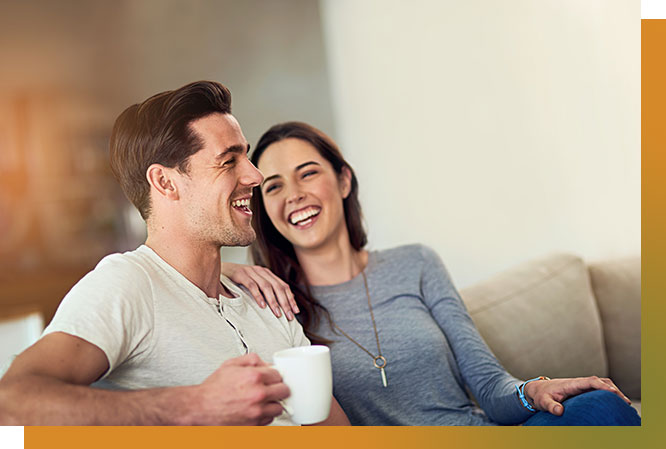 Man and woman relaxing on couch. Both laughing.